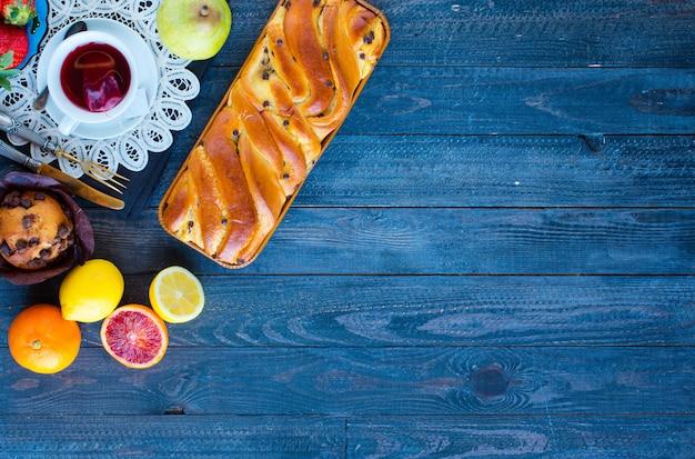 Frühstücken sie mit kaffee und tee mit unterschiedlichem gebäck und früchten auf einem holztisch Premium Fotos