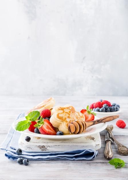 Frühstücken sie mit schottischen pfannkuchen in der blumenform, beeren und honig auf hellem holztisch. Premium Fotos