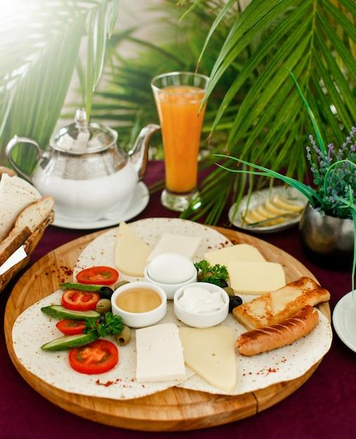 Frühstücksetup mit frühstücksteller, orangensaft und teekanne Kostenlose Fotos