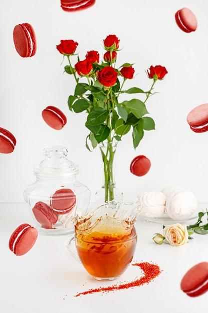 Frühstücksnachtische auf weißem hintergrund mit makronen, blumenstrauß von roten rosen und dem spritzen des tees. Premium Fotos