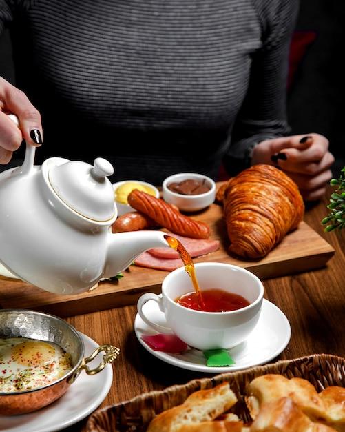 Frühstücksset auf dem tisch mit schwarzem tee Kostenlose Fotos