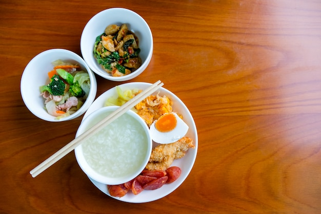 Frühstücksset, gekochter reis in einer schüssel, gebratenes gemüse, gebratene fleischbällchen mit basilikum Premium Fotos