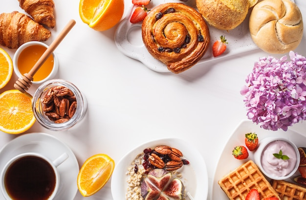 Frühstückstisch mit haferflocken, waffeln, croissants und früchten Premium Fotos