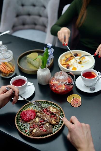 Frühstückstischeinstellung mit pfannkuchen, tee. paar isst Premium Fotos