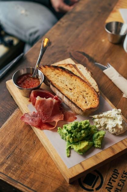 Frühstückstoast mit schinken und avocado an bord Kostenlose Fotos