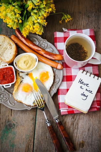 Frühstückszeit mit würstchen, eiern und teetasse Premium Fotos