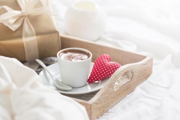 Frühstückstablett mit einem Kaffee, einem Herzen und einem goldenen Geschenk Kostenlose Fotos