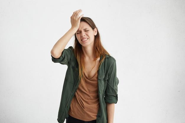 Frustrierte brünette frau, die freizeitkleidung trägt, die hand auf der stirn hält, die depressiv ist und bedauert, was sie getan hat, kopfschmerzen zu haben. verwirrte frau mit gerunzelter stirn, die stressig aussieht und schmerzen hat Kostenlose Fotos