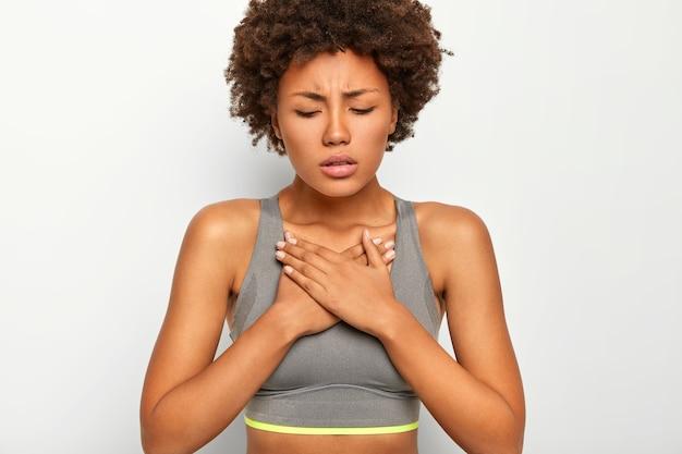 Frustrierte dunkelhäutige afroamerikanische frau leidet unter akuten schmerzen in der brust, trägt grauen sport-bh, isoliert auf weißem hintergrund Kostenlose Fotos