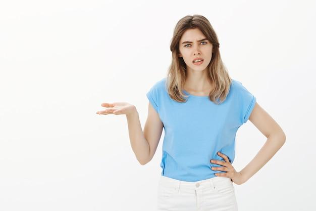 Frustrierte junge frau, die fragt warum, kann es nicht verstehen, besorgt mit den schultern zu zucken Kostenlose Fotos