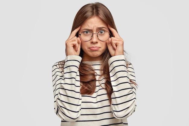 Frustrierte junge frau mit brille, die gegen die weiße wand aufwirft Kostenlose Fotos