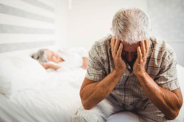 Frustrierter älterer mann, der auf bett im schlafzimmer sitzt Premium Fotos