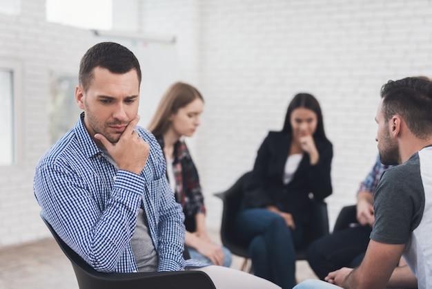Frustrierter erwachsener mann sitzt in der gruppentherapiesitzung. Premium Fotos