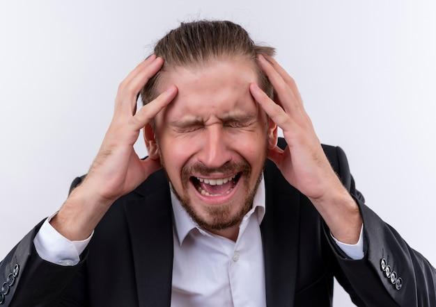 Frustrierter hübscher geschäftsmann, der anzug trägt, der seinen kopf mit den händen steht, die über weißem hintergrund stehen Kostenlose Fotos