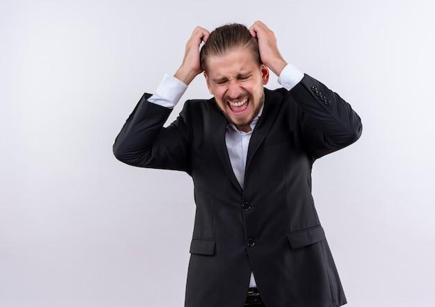 Frustrierter hübscher geschäftsmann, der anzug trägt, der wild geht, indem er sein haar zieht, das über weißem hintergrund steht Kostenlose Fotos