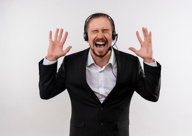 Frustrierter hübscher geschäftsmann in anzug und kopfhörern mit einem mikrofon, das mit aggressivem ausdruck schreit und schreit, der über weißem hintergrund steht Kostenlose Fotos