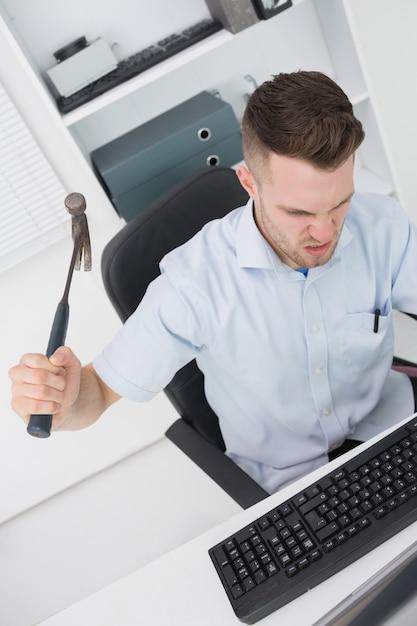 Frustrierter mann, der computermonitortastatur mit hammer schlägt Premium Fotos