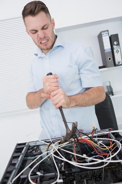 Frustrierter mann, der hammer verwendet, um drähte von cpu herauszuziehen Premium Fotos