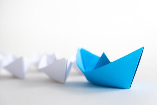 Führungskonzept. blaues papierschiff führen unter weiß. ein führerschiff führt andere schiffe. Premium Fotos