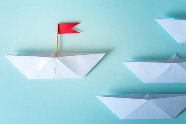 Führungskonzept unter verwendung der papierlieferung mit roter fahne auf blauem hintergrund Premium Fotos