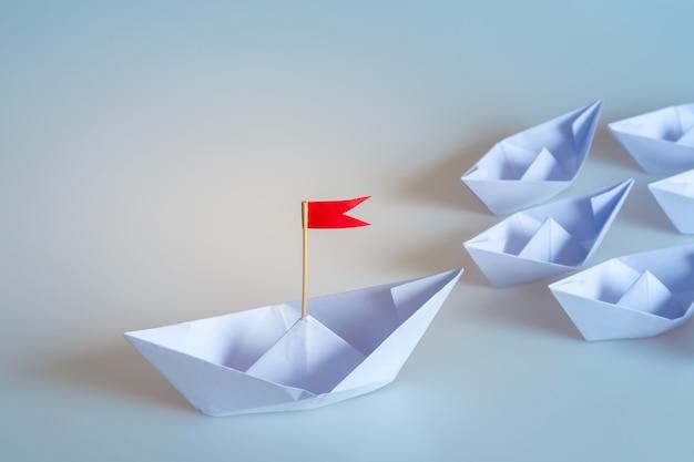 Führungskonzept unter verwendung des papierschiffs mit roter fahne auf blauem hintergrund Premium Fotos