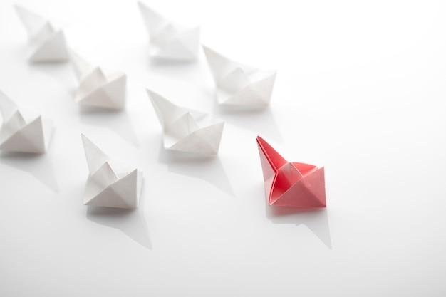 Führungskonzept unter verwendung von papierschiff unter weiß Premium Fotos