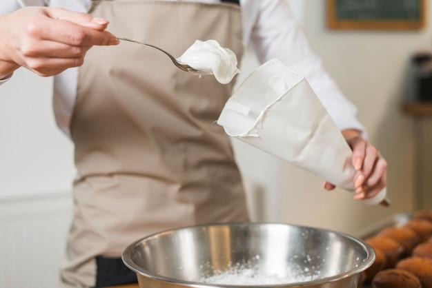 Füllende schlagsahne des weiblichen bäckers im weißen zuckerbeutel Kostenlose Fotos