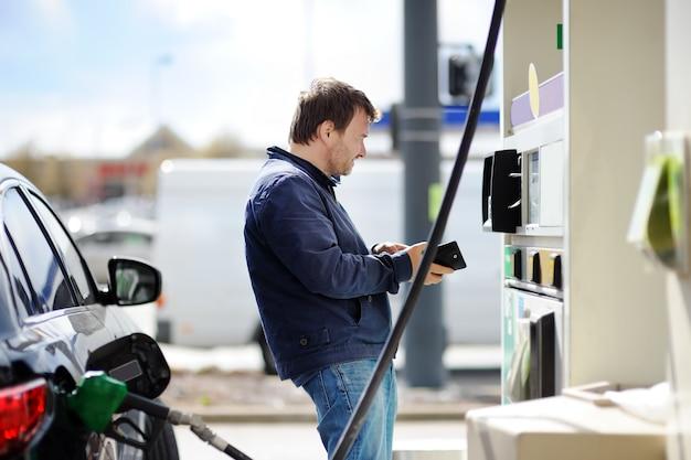 Füllender benzinkraftstoff des mittelaltermannes im auto Premium Fotos