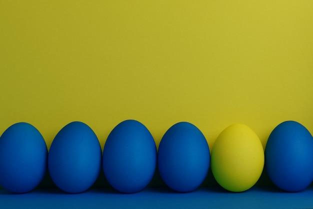 Fünf blaue und ein gelbes gemaltes osterei stehen in folge auf einem gelb mit blauem hintergrund Premium Fotos
