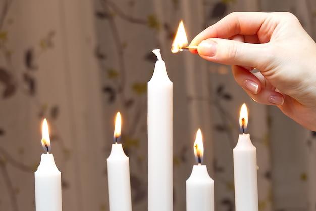Fünf brennende kerzen. frau hand leuchtet kerzen romantische atmosphäre. schöne dekoration. Premium Fotos