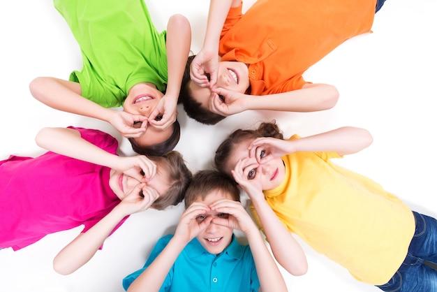 Fünf glückliche kinder liegen auf dem boden in einem kreis mit händen in der nähe von augen in hellen t-shirts. draufsicht. auf weiß isoliert. Kostenlose Fotos