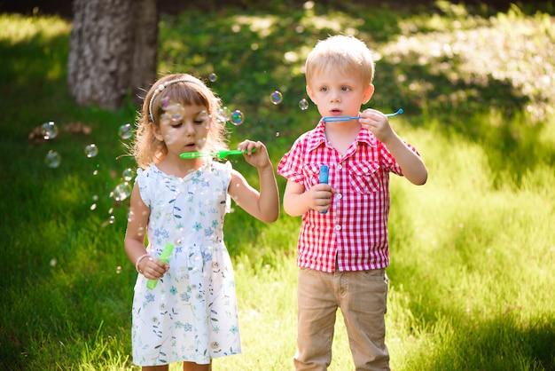 Fünf jahre alte kaukasische schlagseifenblasen des kindermädchens und -jungen Premium Fotos