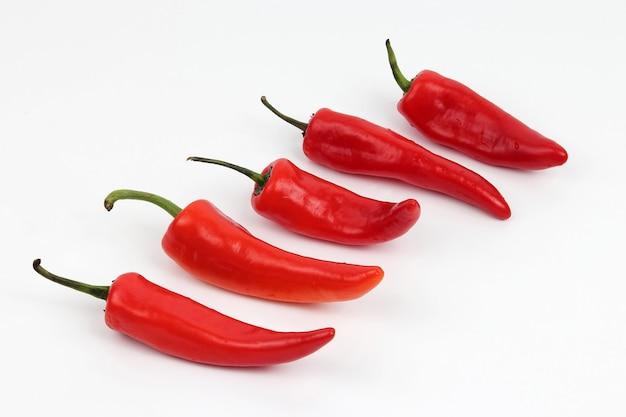 Fünf leuchtend rote paprika isoliert Premium Fotos