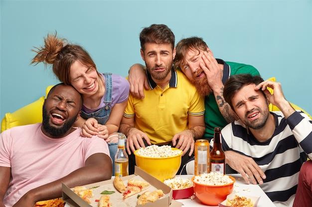 Fünf leute lachen laut, wenn sie sich einen lustigen comedy-film oder eine comic-show ansehen Kostenlose Fotos
