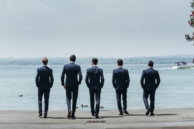 Fünf männer in eleganten anzügen gehen auf das blaue meer zu Kostenlose Fotos