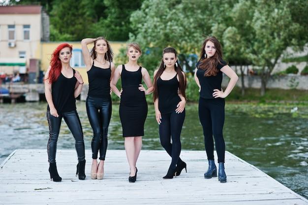 Fünf schöne junge sexy mädchenmodelle im schwarzen festen kleid, das auf pier aufwirft Premium Fotos