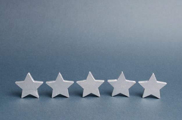 Fünf sterne auf grau. erfolg im geschäft. das konzept der bewertung und bewertung Premium Fotos