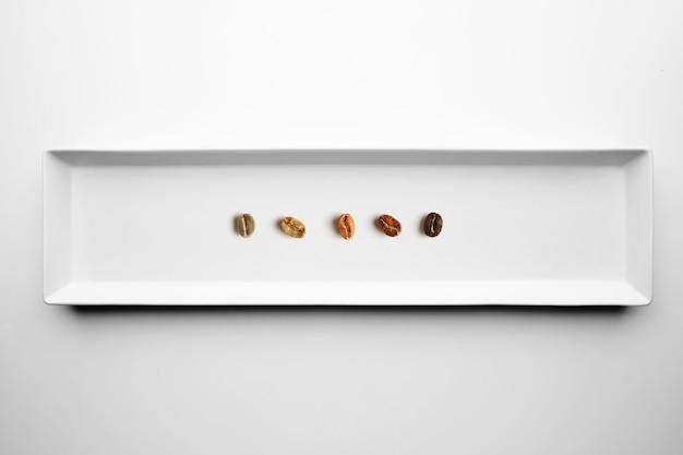 Fünf verschiedene sorten gerösteter kaffeebohnen, aromatisch, von roh bis vollständig geröstet, isoliert auf draufsicht auf weißem teller Kostenlose Fotos