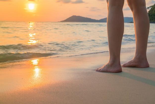 Füße auf dem sand im sonnenuntergang Kostenlose Fotos