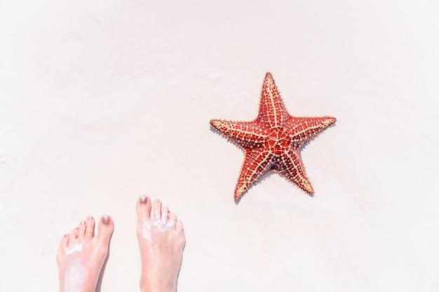 Füße auf tropischem weißem sand mit roten starfish Premium Fotos