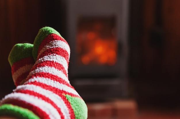 Füße beine im winter kleidet wollsocken am kamin zu hause am winter- oder herbstabend, der sich entspannt und aufwärmt Premium Fotos