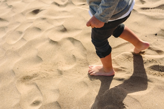 Füße des jungen gehend auf den sand des strandes. Premium Fotos