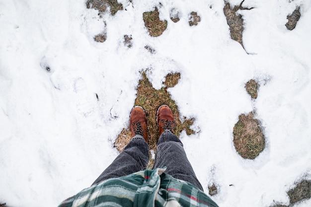 Füße im schnee, sicht. direkt über dem bild eine person in warmer freizeitkleidung bei einem winterspaziergang Premium Fotos