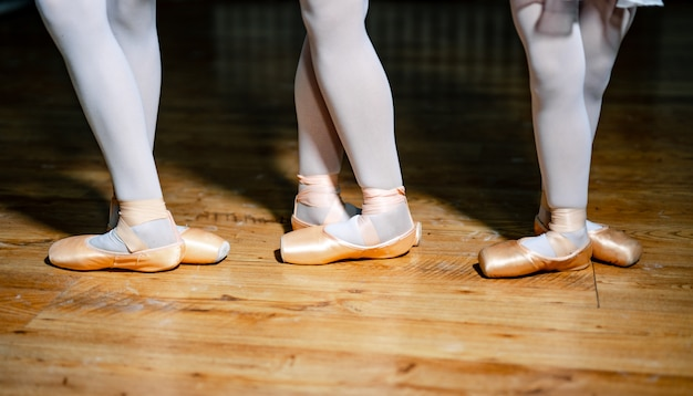 Füße von drei jungen ballerinas in spitzenschuhen Premium Fotos