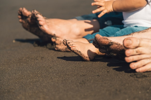 Füße von eltern und baby sitzen am sandstrand Kostenlose Fotos