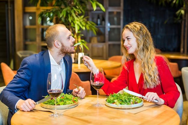 Fütterungsmann der jungen frau mit salat im restaurant Kostenlose Fotos