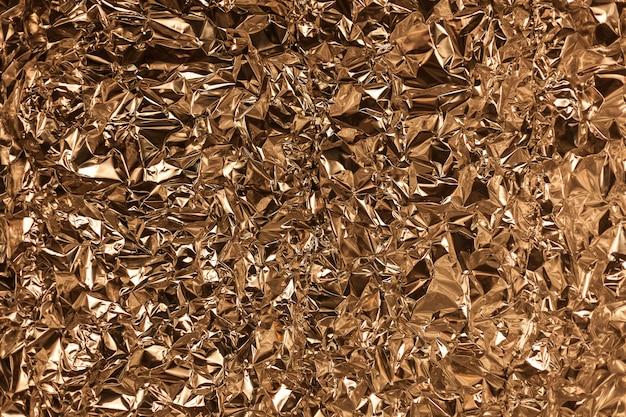 Full-frame-aufnahme eines zerknitterten blattes aus goldener aluminiumfolie Premium Fotos