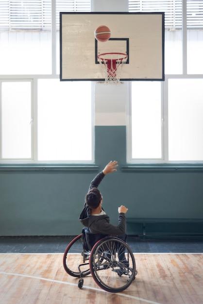 Full shot behinderter mann wirft ball Kostenlose Fotos