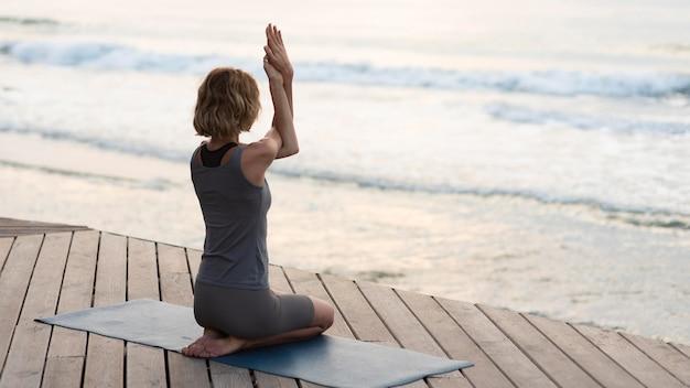 Full shot frau macht yoga-pose auf matte außerhalb Kostenlose Fotos