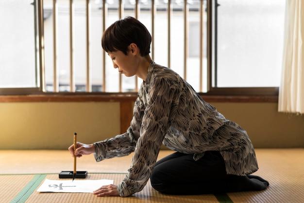 Full shot frau malt japanische buchstaben Premium Fotos
